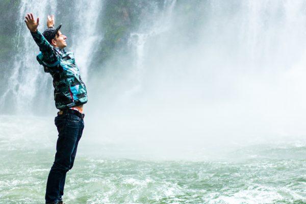 Mann vor Wasserfall