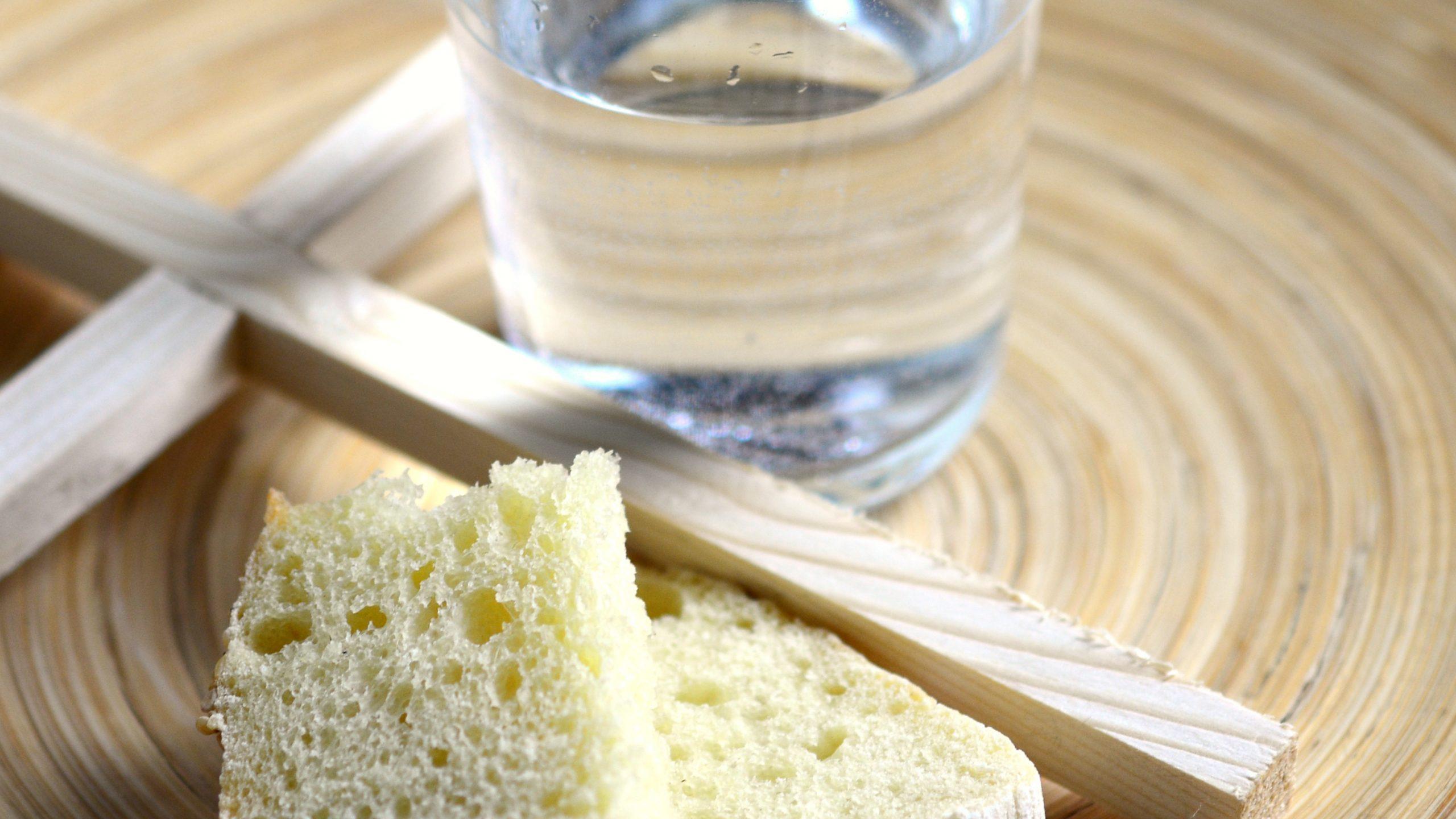 Brot, Wasser und Kreuz auf einem Teller
